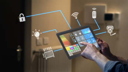 Close up of a man hand is using a futuristic latest innovative technology glass tablet with augmented reality holograms as a remote control of smart home appliances at home or office.