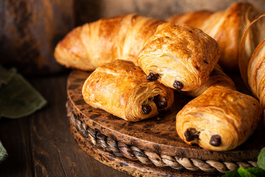 Coffee break with freshly baked sweet buns puff pastry with chocolate and croissants on old wooden background. Breakfast or brunch concept