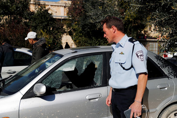 An Israeli policeman looks at a car damaged during a suspected Palestinian shooting attack in which an Israeli policeman was injured lightly in Jerusalem's Old City