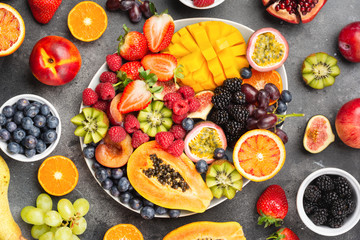 Wall Mural - Delicious fruit platter mango pomegranate raspberries papaya oranges passion fruits berries on oval serving plate on dark concrete background, selective focus, top view