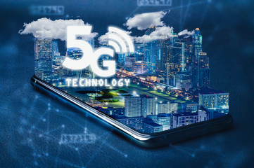 the abstract image of the smartphone laying on the table and overlay with futuristic cityscape and 5G hologram image. the concept of future, 5G, telecommunications, business and internet of things.