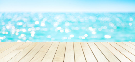 The blur sea and sky background with wood deck or table on the beach.