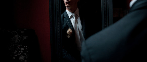 Elegant man clothing of a groom in a mirror reflection in dark