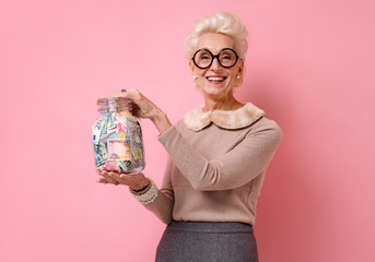 Smiling grandmother shows her saving money in glass jar. Photo of kind elderly woman wears eyeglasses on pink background.