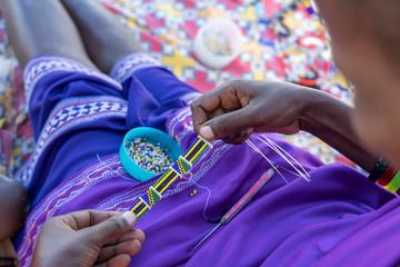 Making of handmade jewellery. Masai african women hands, top view, close up. Island of Zanzibar, Tanzania, Africa