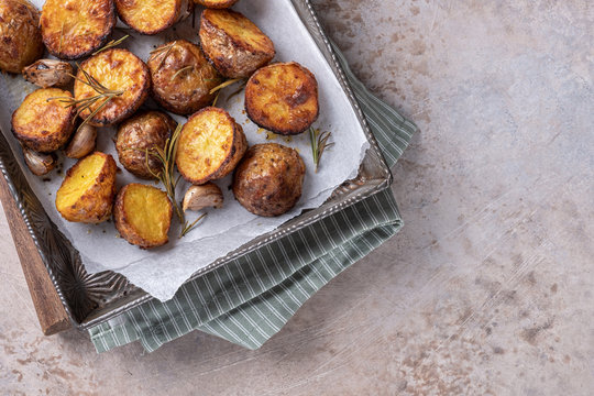 Roasted potato with rosemary on a baking sheet