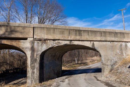 Old rural railroad bridge with crumbling, cracking concrete. Concept of deterioration transportation infrastructure in the United States of America