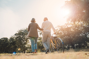 Beautiful Senior couple walking their bike along happily talking in park.mature couple in summer...