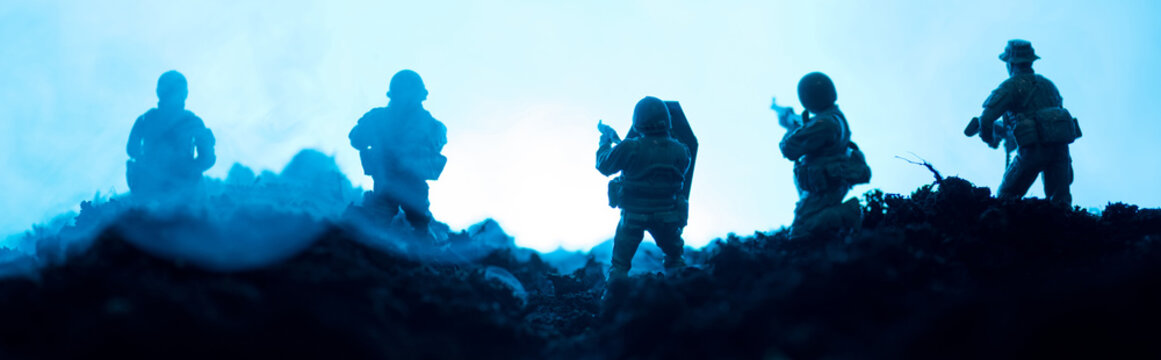 Battle scene of toy soldiers with smoke on blue background, panoramic shot