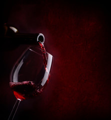 Red wine pouring in wineglass from bottle over dark background.