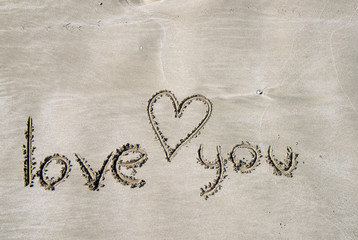 The beach, light dense sand on which the inscription is made in English: I love you. And a heart is drawn. The morning light of the bright sun