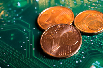 Makro close up of isolated glowing blurred pile euro cent coins on green motherboard