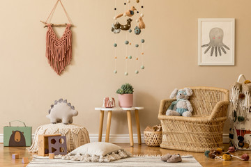Stylish and beige scandinavian decor of kid room with mock up poster frame, design furnitures, natural toys, hanging colorful decor, macrame, teddy bears, plush animal and child accessories. Template