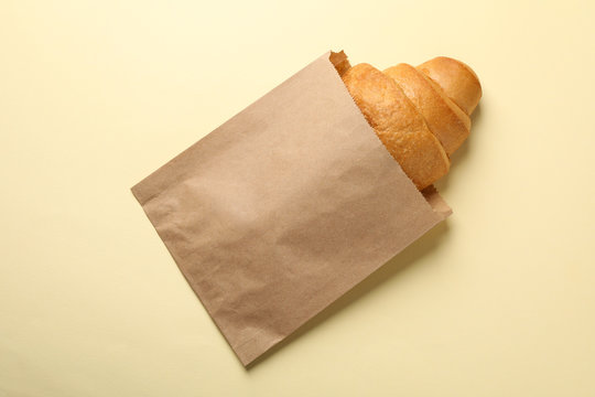 Craft paper bag with croissant on beige background, space for text