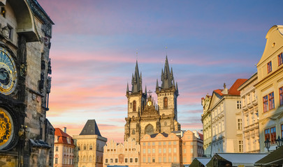 Old Town Prague and town square with the Astonomical Clock and the Our Lady Before Tyn church towers and spires under a colorful sky at sunset.