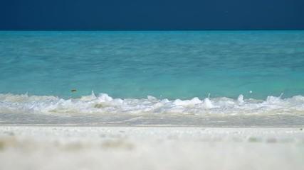 Wall Mural - Blue sea wave breaks on the sandy beach in Maldives