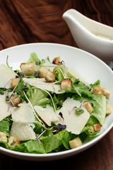 caesar salad with parmesan cheese and croutons on table.
