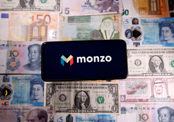 Smartphone with Monzo logo is placed on the banknotes in this illustration