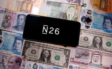 A smartphone displays a N26 logo on top of banknotes is in this illustration