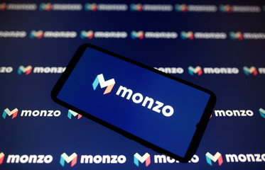 A smartphone displays a Monzo logo in this illustration