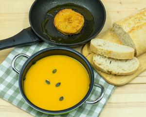 Kürbissuppe im Topf und Bratling in der Pfanne
