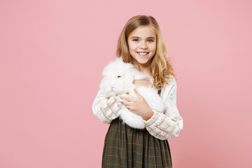 Little pretty blonde kid girl 11-12 years old in light spring dress hold fluffy white bunny rabbit isolated on pastel pink background children studio portrait. Childhood lifestyle Happy Easter concept