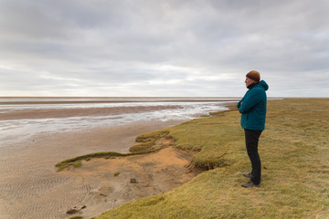 entpannter Mann schaut am Strand in die Ferne