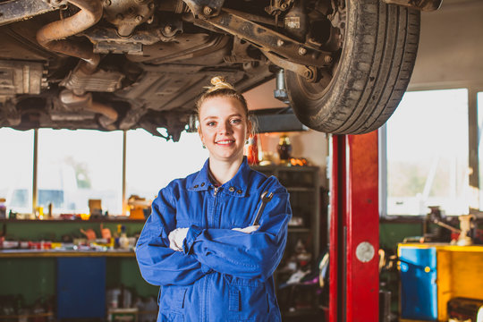 Successful auto mechanic woman at workshop indoor