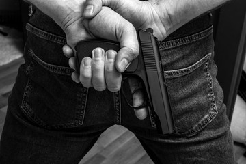 Black and white photo, man in hood with gun or pistol. Gangster, violence, outrage, force, rape or criminal concept, focus on the gun.