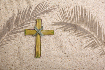 Wall Mural - Palm Sunday. Cross and palm shadows on sand background