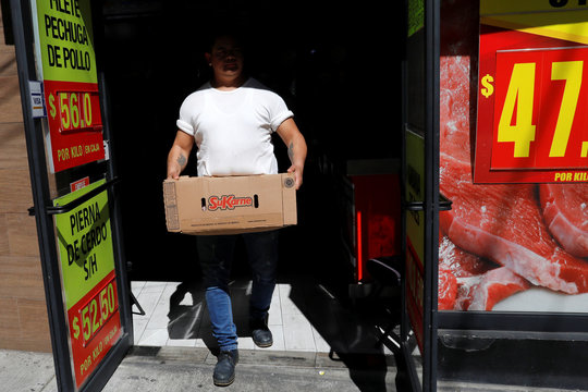 A man carries a beef package with the logo of the Mexican food protein company SuKarne in one of its stores in Mexico City