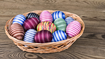 Colored striped ornate Easter eggs in wicker basket on wood. Empty eggshells hand-decorated by glued colorful cotton sewing yarn. Traditional egg shells decoration symbolize Jesus Christ resurrection.