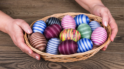 Female hands holding Easter eggs in wicker basket on wooden table detail. Ornate empty eggshells wrapped in colorful cotton thread. Traditional holiday egg shells decorated by glued thin sewing yarn.
