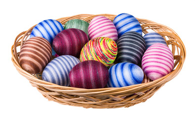 Colorful ornate Easter eggs pile in wicker basket isolated on white background. Hand-decorated striped egg shells wrapped by glued thin cotton sewing yarn. Ornate empty eggshells. Full depth of field.