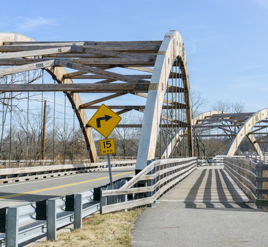 Wooden arch bridge over 2 lane road. Metal bolts and suspender cables. Pedestrian walkway.  Yellow sign with black arrow showing speed limit 15 mph. Blue sky and bare trees background..