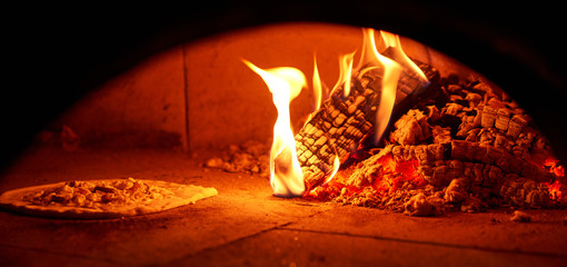 Baked tasty margherita pizza in Traditional wood oven in Naples restaurant, Italy. Original...