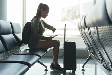 A woman waiting for her deplayed flight at the airport gate. Checking the time.