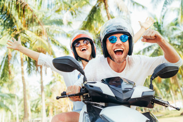 Happy smiling couple travelers riding motorbike scooter in safety helmets during tropical vacation under palm trees on Ko Samui island in Thailand