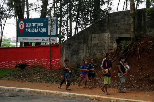 Guarani Mbya indigenous people pass by the builder's billboard as they protest near their land in Sao Paulo