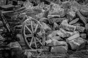 Old wooden cart wheel in stone quarry