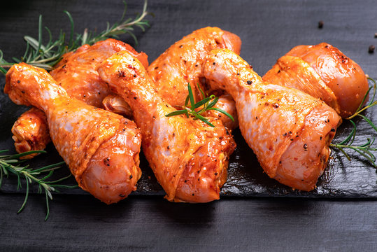 Chicken legs in a red marinade on a cooking board. Pickled raw meat. Dietary meat. Cooking.Raw marinated chicken legs for grill and bbq