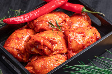 Foto op Canvas Kip Raw chicken quilted in red, tomato marinade on a black plate and spices.Raw meat in the marinade.. Dietary meat. Cooking.Chicken thighs. Spice. Chili pepper .