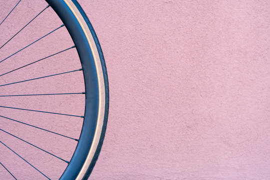 Bicycle wheel on the background of an orange wall. Fashionable fixed bike. Black rim and beige tire. Round object for advertising.