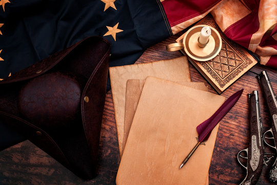 Federalist papers and the birth of the United States of America concept with tricorn hat, candle, feather quill, musket gun, the Betsy Ross American flag and aged paper with copy space