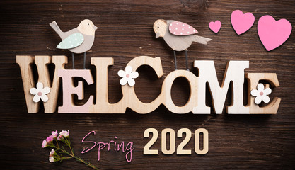 Welcome spring 2020 sign on wooden background