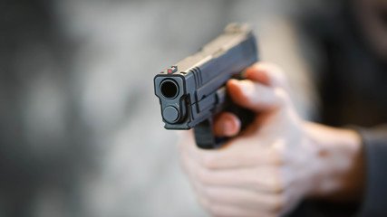 Man holding pistol in firing position. Personal Defense Concept