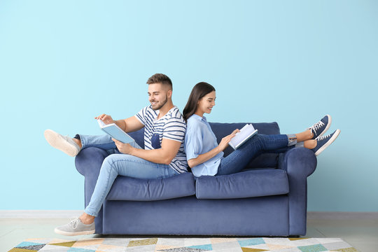 Young couple reading books while sitting on sofa at home