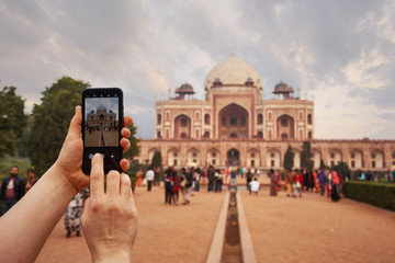 Tourist taking a picture in a smartphone of Humayun's tomb in Delhi, India.