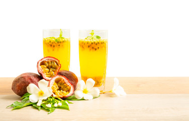 Two glass of passionfruit juice with mint and group of purple skin passionfruit plant, sliced and round fruits on wooden table, isolated on white background, die cut with clipping path image