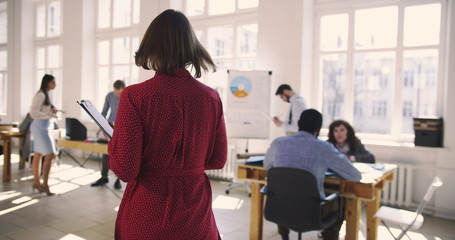Camera follows middle aged business assistant woman in red dress entering large trendy loft office talking to colleagues